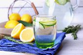 stock photo of cucumber  - Fresh water with lemon and cucumber in glassware on napkin on wooden table - JPG