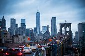 picture of skyscrapers  - Traffic on Brooklyn bridge and New York City Manhattan downtown skyline at dusk with skyscrapers over East River panorama - JPG