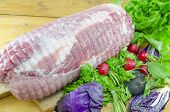 pic of meatloaf  - Raw meatloaf on a cutting board decorated with red radishes lettuce and cabbage - JPG