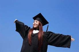 picture of graduation gown  - happy graduate student girl hug future and feel carefree look up to copy space she wear graduation cap and gown asian - JPG