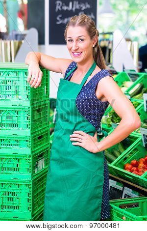 Female Supermarket clerk filling up storage racks in vegetable department