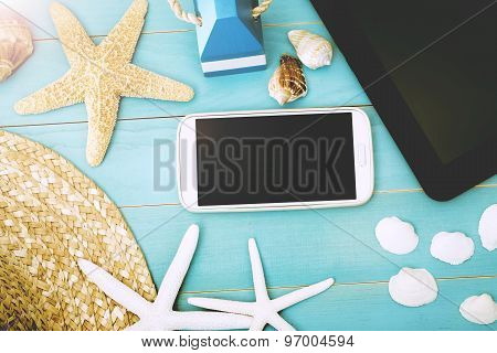 Gadgets On The Table With Starfish, Shells And Hat