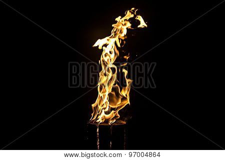 Image of glowing log, flame by night