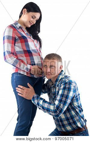 Photo of man listening belly, pregnant woman