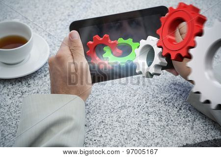 Businessman holding small tablet at table against white and red cogs and wheels
