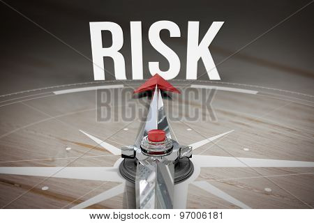 The word risk and compass against brown wooden background