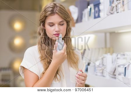 A pretty blonde woman in a perfumery at the mall