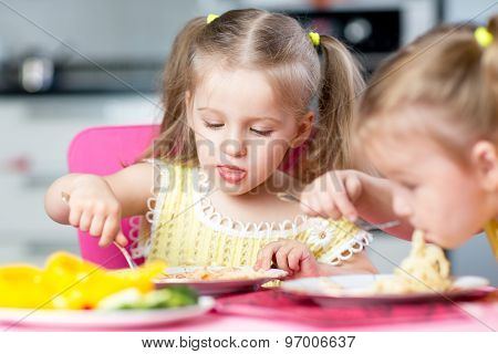 Kids eating spaghetti with vegetables in nursery