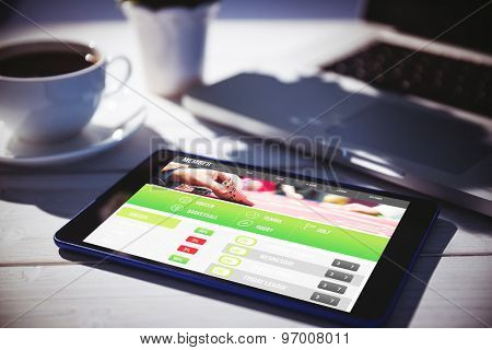 Gambling app screen against tablet and laptop on table