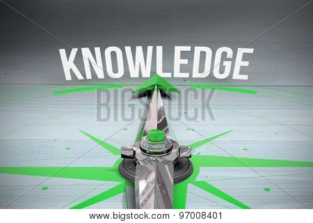The word knowledge and compass against bleached wooden planks background