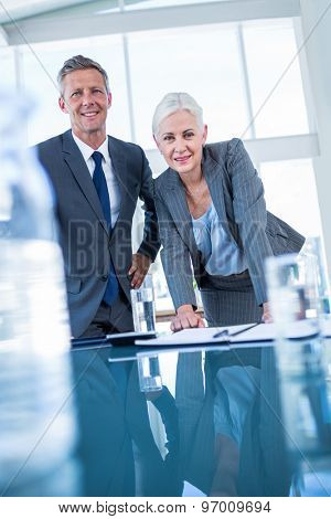 Business people looking at camera behind desk in office