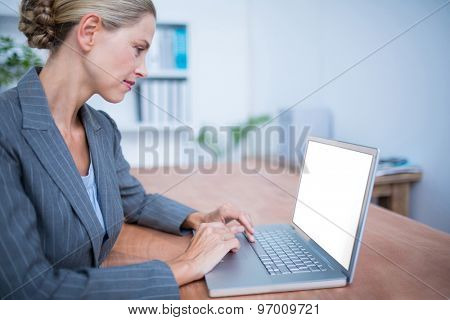 Side view of an attentive businesswoman working on laptop