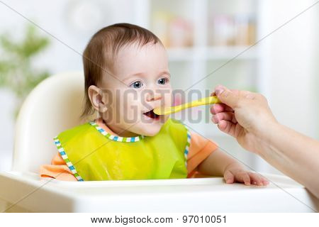 Pretty kid eating with spoon