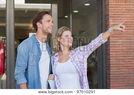 Happy couples looking and pointing far away at the mall