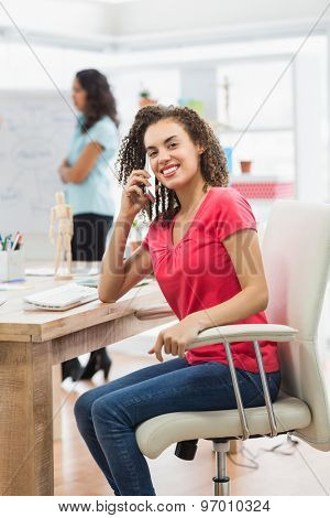 Businesswoman calling someone at her desk in the office