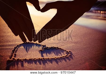 Woman making heart shape with hands against one heart drawn in the sand