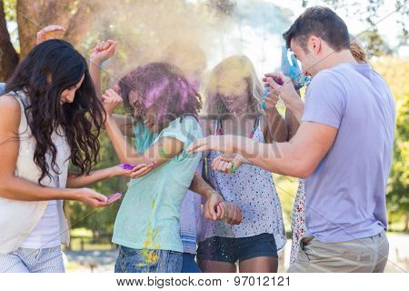 Friends throwing powder paint on a sunny day
