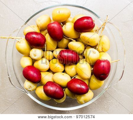 Freshly plucked date palms (yellow and red variety) fruit kept on a bowl on an plain background
