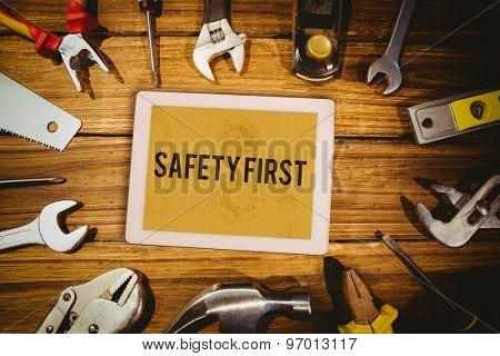 The word safety first and tablet pc against architect background