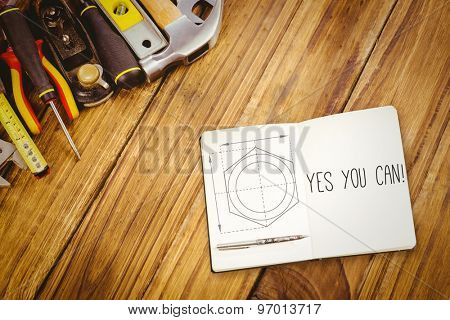 The word yes you can! and notebook and pen against blueprint