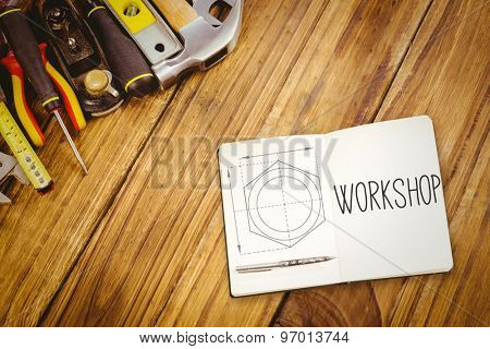 The word workshop and notebook and pen against blueprint