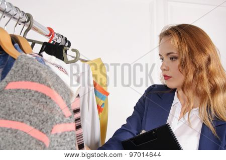 Girl In Formal Wear Chooses Shirt In A Clothing Store