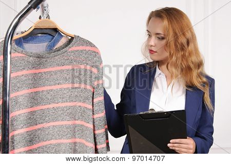 Woman In Formal Clothes Chooses Shirt In A Clothing Store