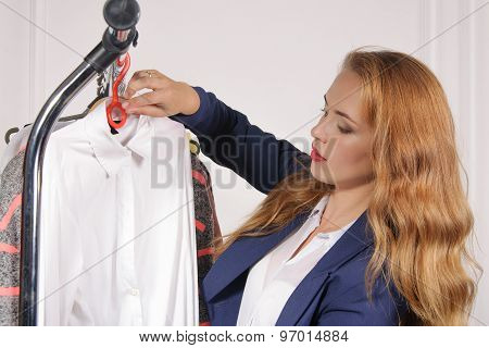 Woman In Formal Wear Takes His Shirt Off The Rack