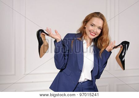Woman In Formal Wear Holding In Each Hand Shoes