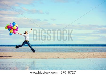 Beautiful girl jumps on the beach while holding colored balloons