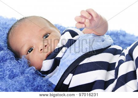 Close-up of an adorable newborn boy looking at the viewer with bright eyes as he's swaddled in a striped blanket and laying on a fluffy blue pad.  On a white background.