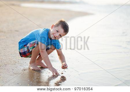 Little Boy Squat On Beach