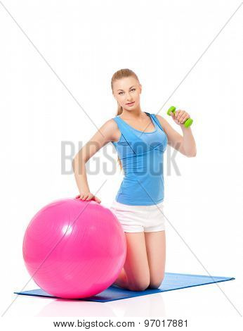 Young woman in fitness wear exercising with fitness-ball and dumbbells, isolated on white background