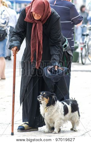Old Italian Beggar With Her Dog