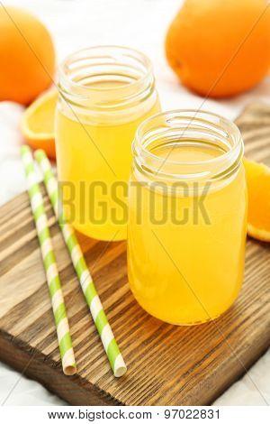 Orange Juice In Bottle On Cutting Board