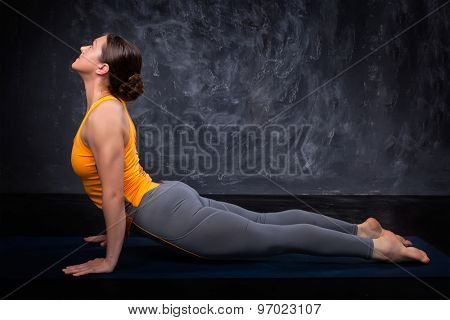 Beautiful sporty fit yogini woman practices yoga asana urdhva mukha svanasana - upward facing dog pose on dark background