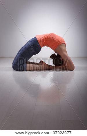 Beautiful sporty fit yogini woman practices yoga asana Kapotasana - pigeon pose intense backbend in studio