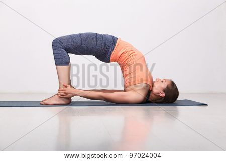 Beautiful sporty fit yogini woman practices yoga asana setu bandhasana - bridge pose advanced variation in studio