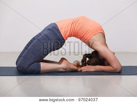 Beautiful sporty fit yogini woman practices yoga asana Kapotasana - pigeon pose intense backbend in studio