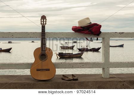 The guitar and backpack on a pier