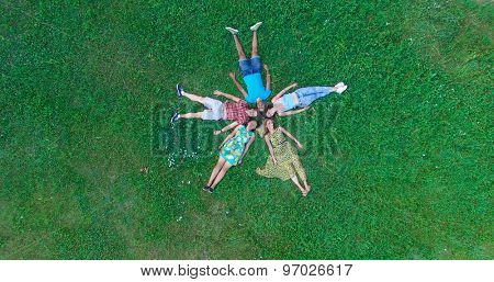 Group of young adults laying in grass in star formation shot from above with drone