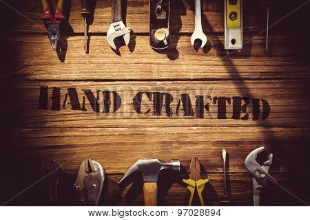 The word hand crafted against desk with tools