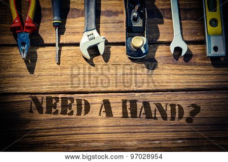 The word need a hand? against desk with tools