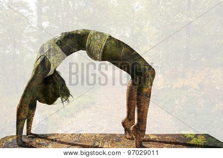 Gorgeous fit blonde in crab pose against scenic view of walkway along lush forest