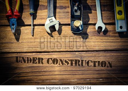 The word under construction against desk with tools