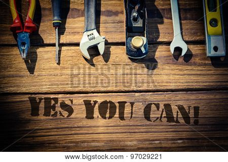 The word yes you can! against desk with tools