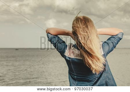 Rear View Of Young Blond Woman Looking At The Ocean