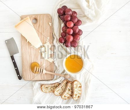 Parmesan cheese with grapes, honey and bread slices on wooden chopping board over rustic white backg