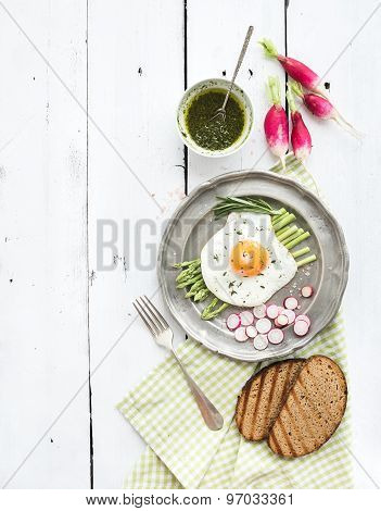 Healthy breakfast set. Fried egg with asparagus, radishes, green sauce and bread on vintage metal pl