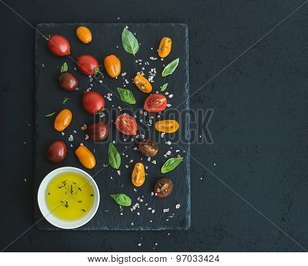 Cherry tomatoes of various color, basil leaves, spices and olive oil on black slate tray over dark g
